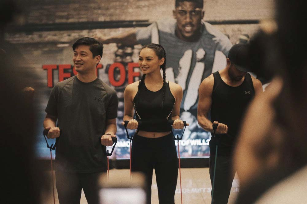 Kylie Versoza and Derek Ramsey pose for Under Armour